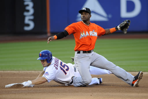 Miami Marlins shortstop Adeiny Hechavarria, top, falls on New York Mets' Travis d'Arnaud (15) after forcing out d'Arnaud at second base in Game 1 of a doubleheader baseball game at Citi Field on Saturday, Sept. 14, 2013, in New York. Hechavarria's throw to first base was not in time for a double play. (AP Photo/Kathy Kmonicek)