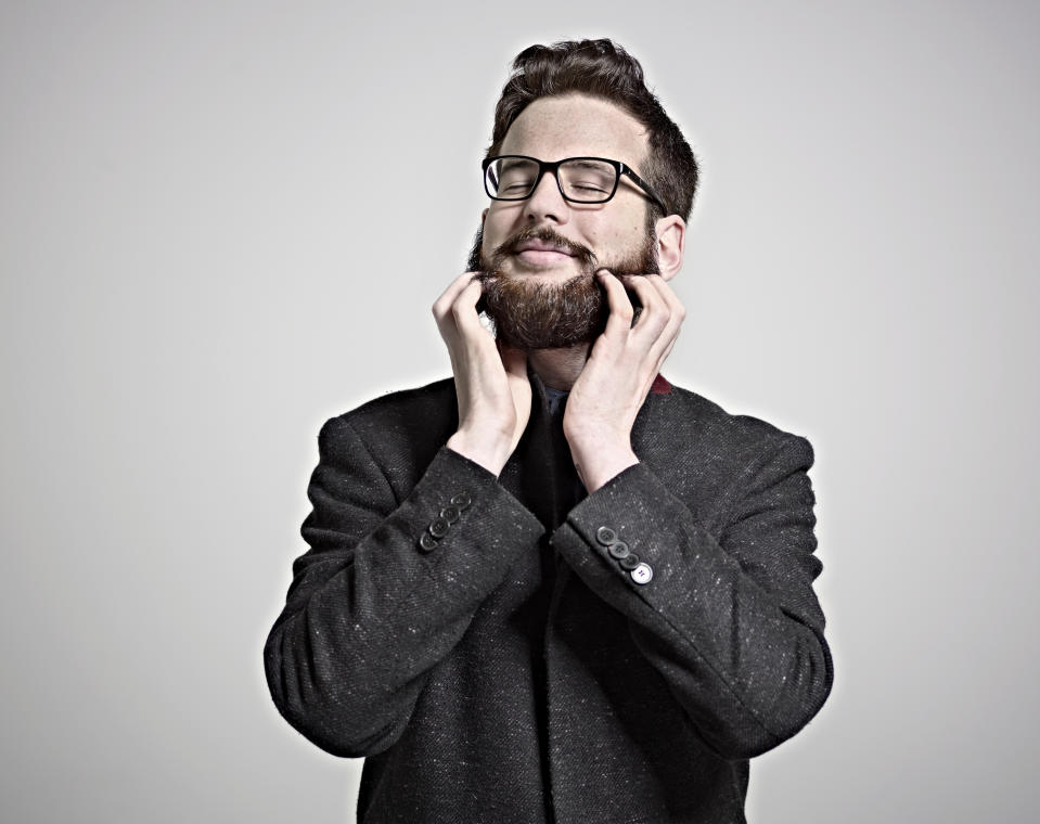 Portrait of smartly dressed man in black overcoat and glasses feeling his beard with eyes closed, smiling.
