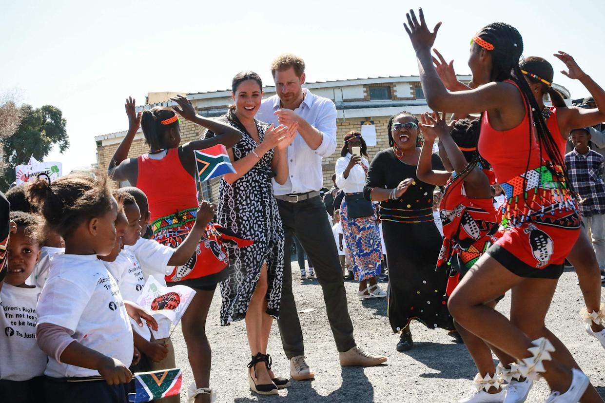 Prince Harry and Duchess Meghan dance as they arrive for a visit to the Justice Desk in Cape Town as they begin their tour of the region.
