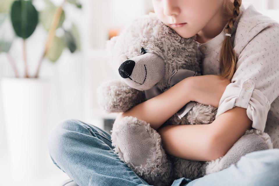 cropped shot of depressed little child embracing her teddy bear