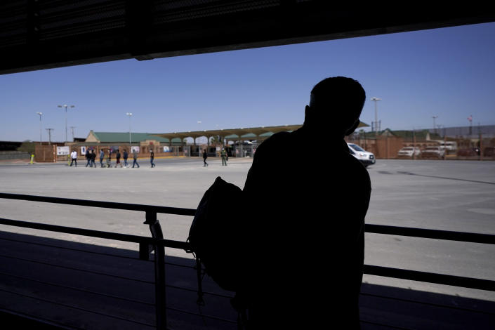 """A traveler, right, waiting in line Thursday, March 18, 2021, in Hidalgo, Texas to cross a customs area into the U.S. at the McAllen-Hidalgo International Bridge looks back as a group of migrants are deported to Reynosa, Mexico. The fate of thousands of migrant families who have recently arrived at the Mexico border is being decided by a mysterious new system under President Joe Biden. U.S. authorities are releasing migrants with """"acute vulnerabilities"""" and allowing them to pursue asylum. But it's not clear why some are considered vulnerable and not others. (AP Photo/Julio Cortez)"""