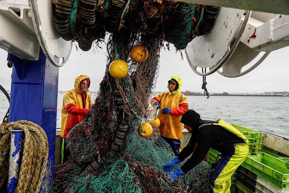 French fishermen gather in a net on their vessel near the port of Saint Helier, JerseyAFP via Getty Images