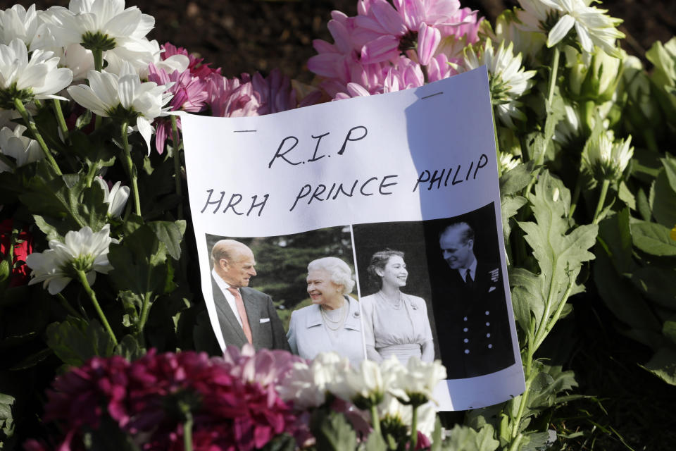 A message is left amoungst flowers outside Windsor Castle in Windsor, England Sunday, April 11, 2021. Britain's Prince Philip, the irascible and tough-minded husband of Queen Elizabeth II who spent more than seven decades supporting his wife in a role that mostly defined his life, died on Friday. (AP Photo/Kirsty Wigglesworth)