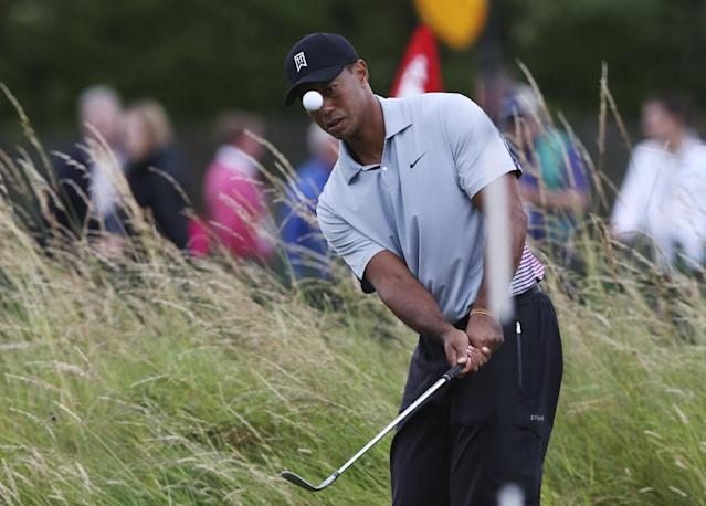 10ThingstoSeeSports - Tiger Woods watches his shot on the practice chipping green ahead of the British Open Golf championship at the Royal Liverpool golf club, Hoylake, England, Wednesday July 16, 2014. (AP Photo/Jon Super, File)