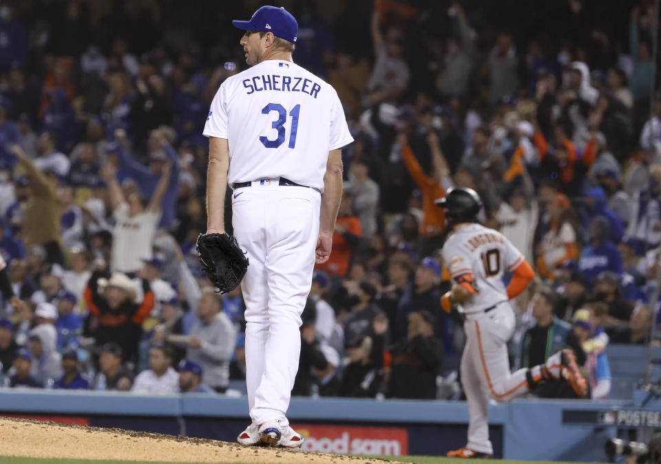 Los Angeles, CA - October 11: Los Angeles Dodgers starting pitcher Max Scherzer, left, looks back after allowing a solo home run to San Francisco Giants' Evan Longoria during the fifth inning in game three of the 2021 National League Division Series at Dodger Stadium on Monday, Oct. 11, 2021 in Los Angeles, CA.(Robert Gauthier / Los Angeles Times via Getty Images)