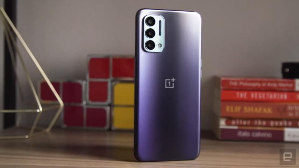 <p>OnePlus Nord N200 5G review picture. Off angle view of the phone sitting on a shelf with ornaments in the background with its rear facing outwards. </p>