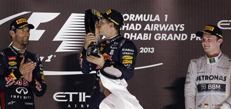 Red Bull Formula One driver Sebastian Vettel of Germany (C) kisses his trophy after winning the Abu Dhabi F1 Grand Prix at the Yas Marina circuit on Yas Island, November 3, 2013. REUTERS/Caren Firouz
