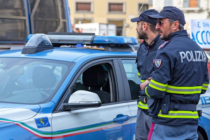 Florence, Italy - April 02 2019: Two officers of the Polizia Stradale near their car. The Polizia Stradale is the national highway patrol of Italy and is a sub-directorate of the Italian State Police.
