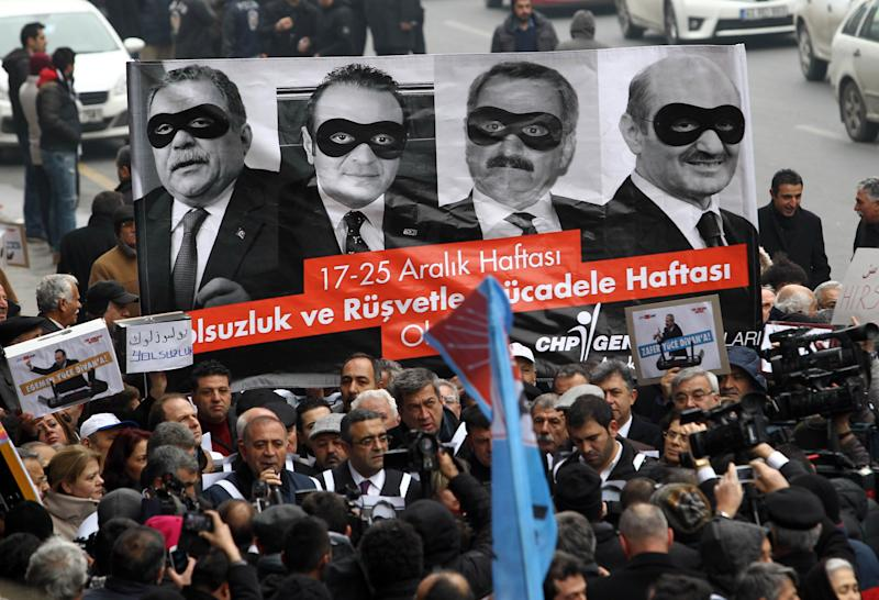 Supporters of main opposition party CHP hold a banner bearing pictures of four former ministers during a protest against corruption and bribery, on December 17, 2014 in Ankara (AFP Photo/Adem Altan)