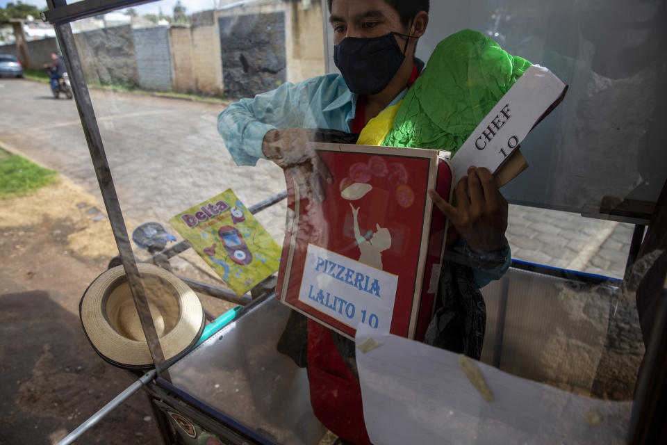 """Standing behind the plexiglass window of his mobile classroom, Gerardo Ixcoy holds a pizza box as part of a lesson on fractions, in Santa Cruz del Quiche, Guatemala, Wednesday, July 15, 2020. """"I tried to get the kids their work sheets sending instructions via WhatsApp, but they didn't respond,"""" Ixcoy said. """"The parents told me that didn't have money to buy data packages (for their phones) and others couldn't help their children understand the instructions."""" (AP Photo/Moises Castillo)"""