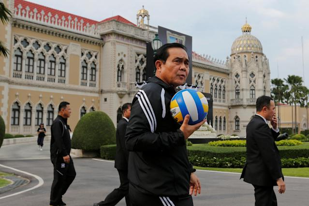 Thailand's Prime Minister Prayuth Chan-ocha plays with a volleyball alongside officials to promote weekly exercise among government officials to foster good health, at the Government House in Bangkok, Thailand, November 23, 2016. REUTERS/Chaiwat Subprasom