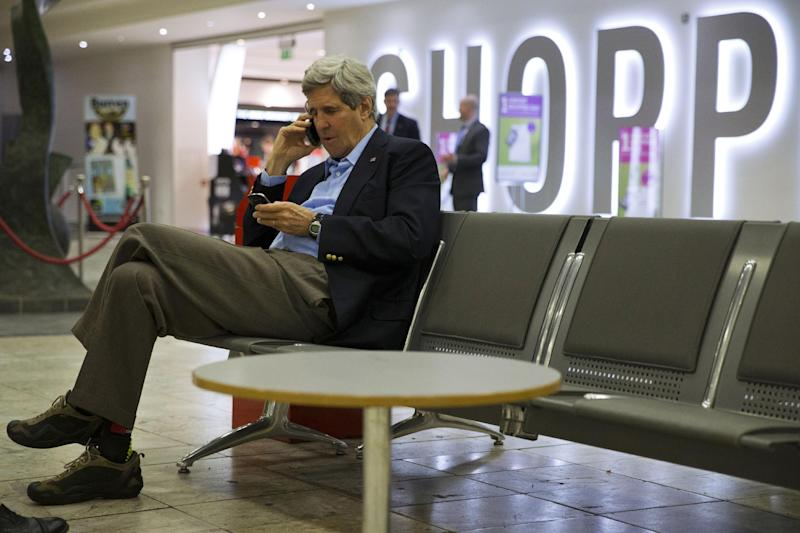 U.S. Secretary of State John Kerry speaks on his cell phone at Shannon Airport in Ireland, Saturday March 29, 2014, during a refueling stop. Halfway home from Saudi Arabia, Kerry has abruptly changed course and will stay in Europe for talks on the Ukraine crisis. Flying from Riyadh to Shannon, for a refueling stop on Saturday, Kerry decided to turn his plane around and was traveling to Paris for a meeting with Lavrov scheduled for Sunday evening.. (AP Photo/Jacquelyn Martin, Pool)