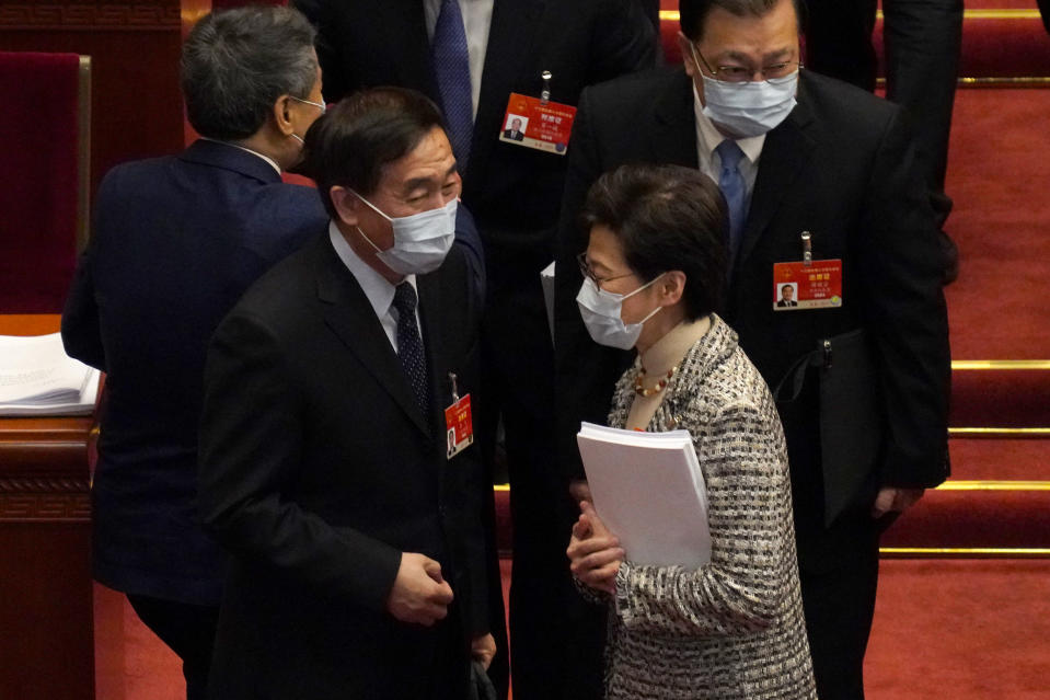 Hong Kong Chief Executive Carrie Lam, right, talks with fellow delegates after the opening session of China's National People's Congress (NPC) at the Great Hall of the People in Beijing, Friday, March 5, 2021. (AP Photo/Andy Wong)
