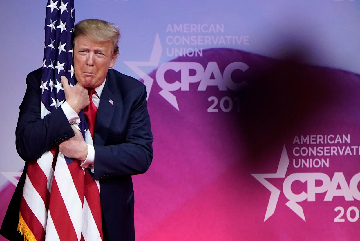 President Trump hugs the flag at the Conservative Political Action Conference annual meeting, March 2, 2019. (Photo: Joshua Roberts/Reuters)