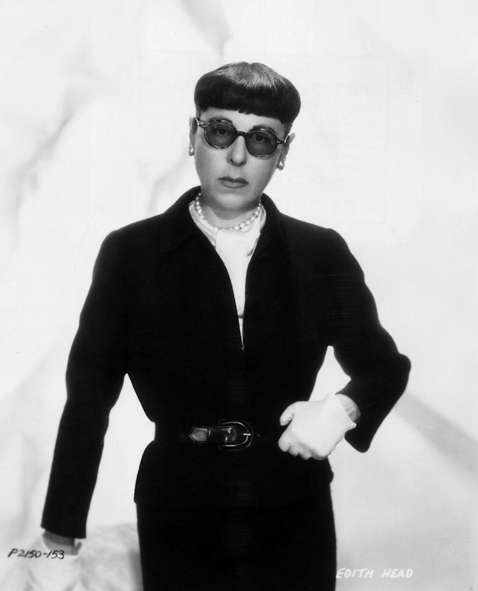 <p>American costume designer Edith Head wearing an all-black belted outfit with white gloves and a string of classic pearls.</p>