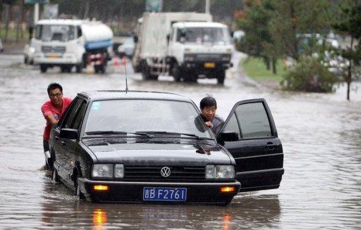 Men push a car through floodwater in Jilin, northeast China's Jilin province in August. Asia's cities are becoming increasingly vulnerable to natural disasters as they struggle with poor planning, population explosions and climate change, the Asian Development Bank warned on Tuesday