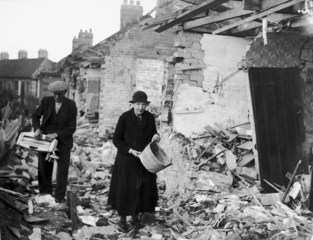 An elderly couple clear away the rubble near their homes after an air raid by the German Luftwaffe on a residential area of Newcastle in 1941. (Getty Images)