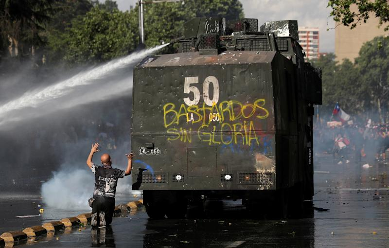Demonstrators are sprayed by riot police with a water cannon during an anti-government protests in Santiago, Chile on Oct. 28, 2019. (Photo: Edgard Garrido/Reuters)