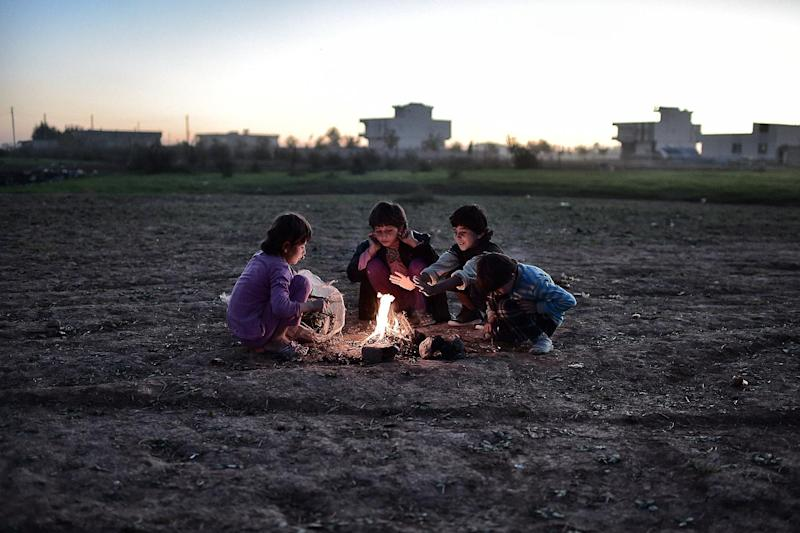Syrian Kurdish children refugees try to get warm around a fire at a refugee camp in the town of Suruc, Sanliurfa province, on November 7, 2014 (AFP Photo/Aris Messinis)