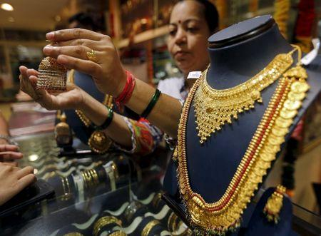 A saleswoman shows a gold earring to customers at a jewellery showroom in Mumbai