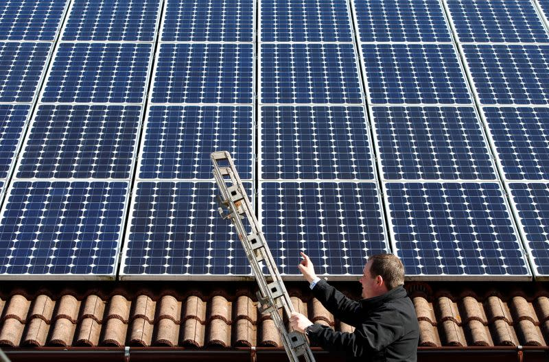 FILE PHOTO: Michael Greif controls his 56 photovoltaic (solar) panels at the roof of his house in Coburg