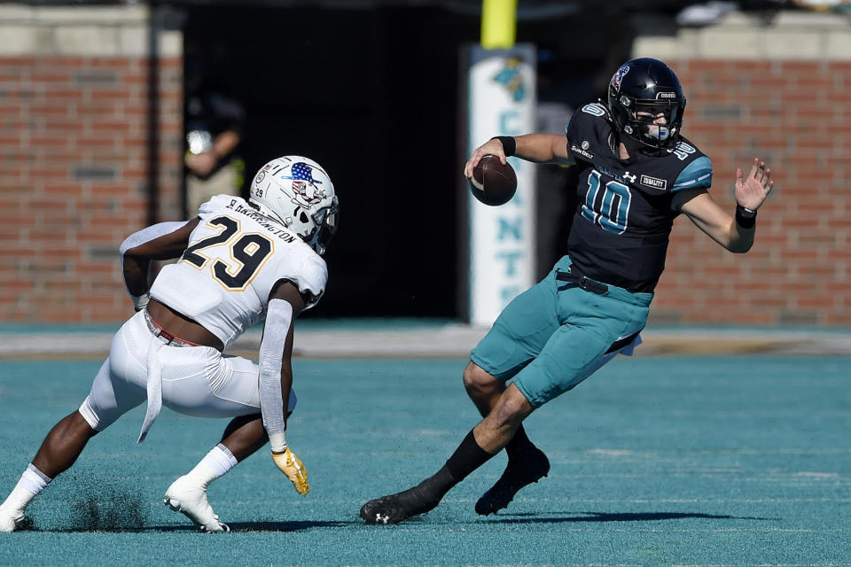 Coastal Carolina quarterback Grayson McCall (10) scrambles as Appalachian State's Brendan Harrington pursues during the first half of an NCAA college football game, Saturday, Nov. 21, 2020, in Conway, S.C. (AP Photo/Richard Shiro)