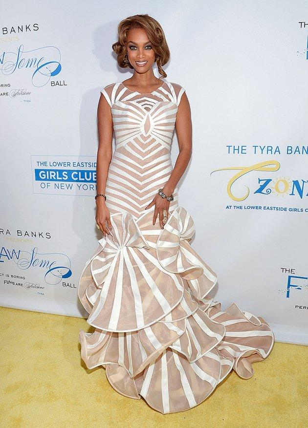 "We love Tyra Banks' dedication to helping young women empower themselves, which she continued to do at Thursday night's Flawsome Ball in NYC. However, we aren't fond of the ""Top Model"" mastermind's consistent need to make a statement (read: make everything about herself) on the red carpet, especially when it involves a chintzy-looking, bedspread-like gown as dizzying and overly ruffled as this one. (10/18/2012)"