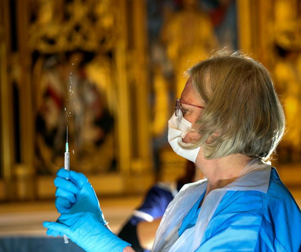 The Pfizer coronavirus vaccine is prepared by a healthcare worker at Salisbury Cathedral, Wiltshire.
