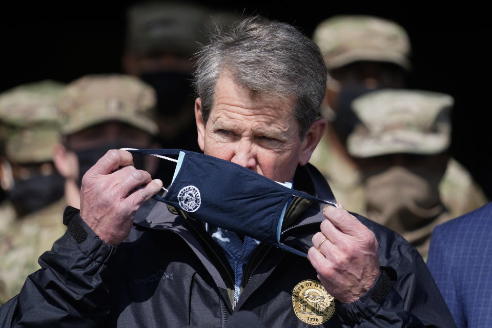 "FILE - In this Feb. 19, 2021, file photo, Georgia Gov. Brian Kemp removes his face covering as he prepares to speak to reporters at the Macon State Farmers Market in Atlanta. The COVID-19 relief package passed by Congress contains a windfall for state governments. But some Republican governors are complaining about the formula used to dole out the money. ""Instead of using the bipartisan blueprint of previous federal coronavirus relief bills, this legislation is literally a wish list for California and New York,"" Kemp said. ""And quite honestly, it's a slap in the face for my fellow Georgians."" (AP Photo/John Bazemore, File)"
