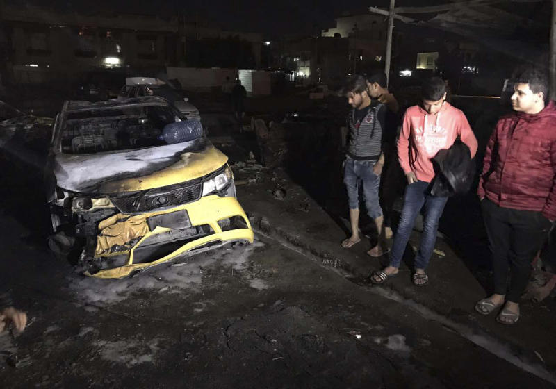 Civilians gather at the site of a car bomb in a used car dealer's parking lot in the southwestern al-Bayaa neighborhood, Baghdad, Iraq, Thursday, Feb. 16, 2017. (AP Photo/ Ali Abdul Hassan)