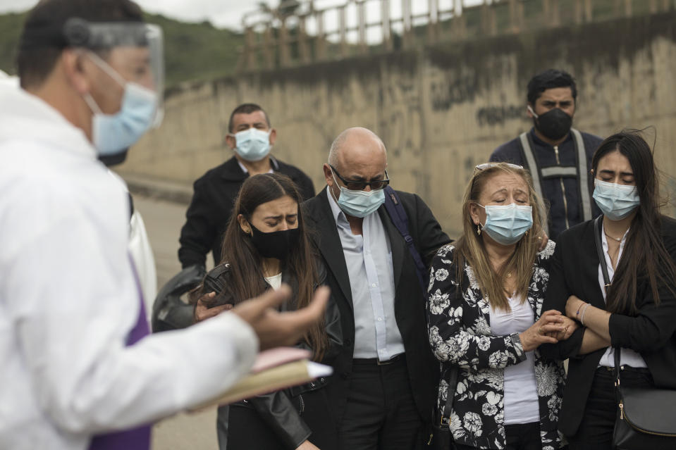 Relatives of COVID-19 victim Miryam Rodriguez listen to prayer outside Serafin Cemetery before her body is cremated in Bogota, Colombia, Friday, June 18, 2021. According to the regulations to contain the new coronavirus, relatives cannot enter the cemetery. (AP Photo/Ivan Valencia)