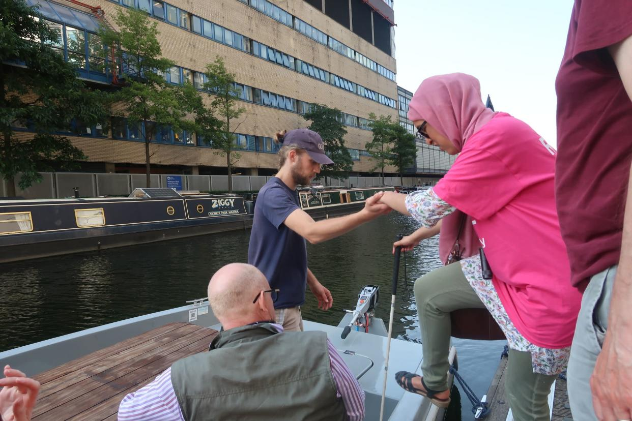 A RNIB member going onto a boat, aided by a crew member.