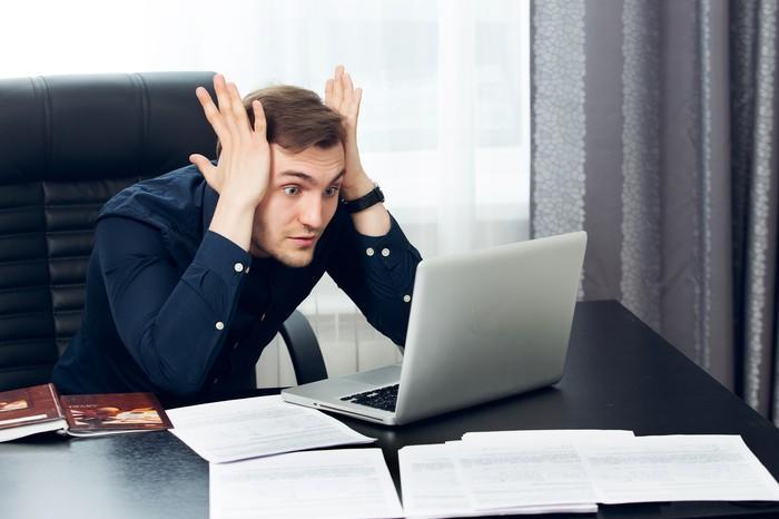 A young businessman at his desk, clutching his head and staring wide-eyed at his computer screen.