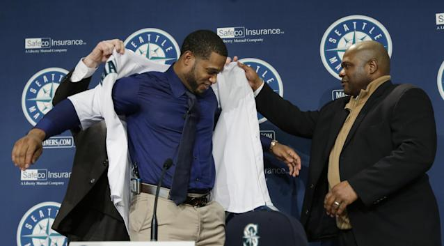 Robinson Cano, center, is helped into his new Seattle Mariners jersey by manager Lloyd McClendon, right, and general manager Jack Zduriencik, left, after being introduced as the newest member of the baseball team, Thursday, Dec. 12, 2013, in Seattle. (AP Photo/Ted S. Warren)