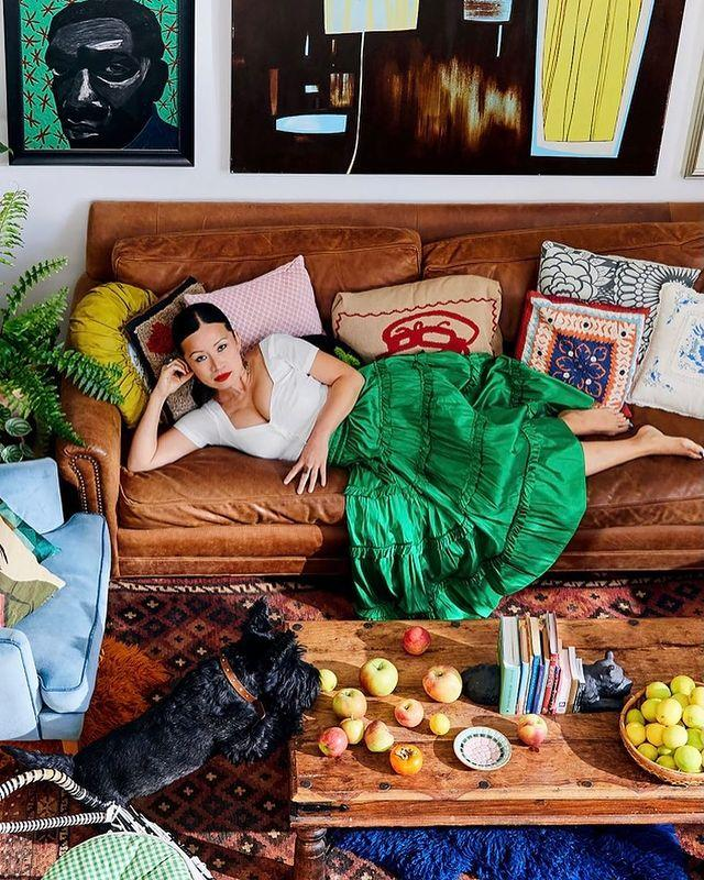MasterChef star Poh Ling Yeow poses in a white top and green skirt on a brown leather couch