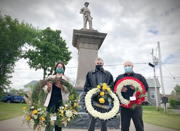 NDP MLA Kendra Coombes, retired union rep Bob Burchell and CBRM Coun. Darren O'Quinn laid wreaths at the Miner's Memorial in New Waterford on Davis Day. (Tom Ayers/CBC - image credit)