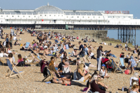 <p>Beach lovers wasted no time in heading down to Brighton (Picture: REX) </p>