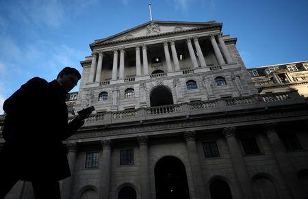 FILE PHOTO: A man walks past the Bank of England in the City of London, Britain, February 7, 2019. REUTERS/Hannah McKay/File Photo