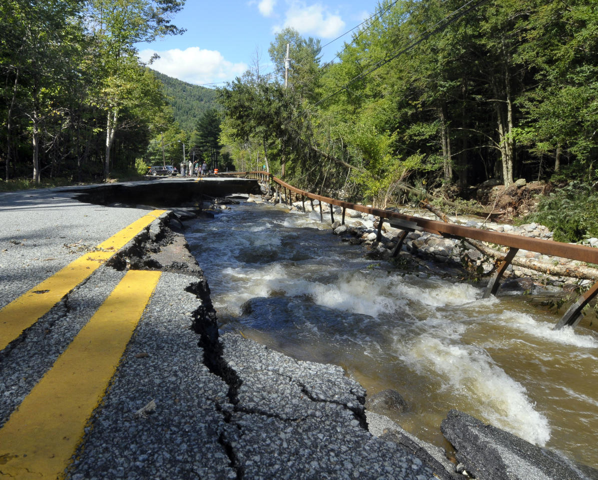 Locals survey the damage caused by Tropical Storm Irene on Route 73 in St. Huberts, N.Y., Monday, Aug. 29, 2011. (AP Photo/Hans Pennink)