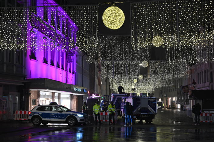 Police officers and firefighters stay together at the scene of an incident in Trier, Germany, Tuesday, Dec. 1, 2020. German police say people have been killed and several others injured in the southwestern German city of Trier when a car drove into a pedestrian zone. Trier police tweeted that the driver had been arrested and the vehicle impounded. (Harald Tittel/dpa via AP)