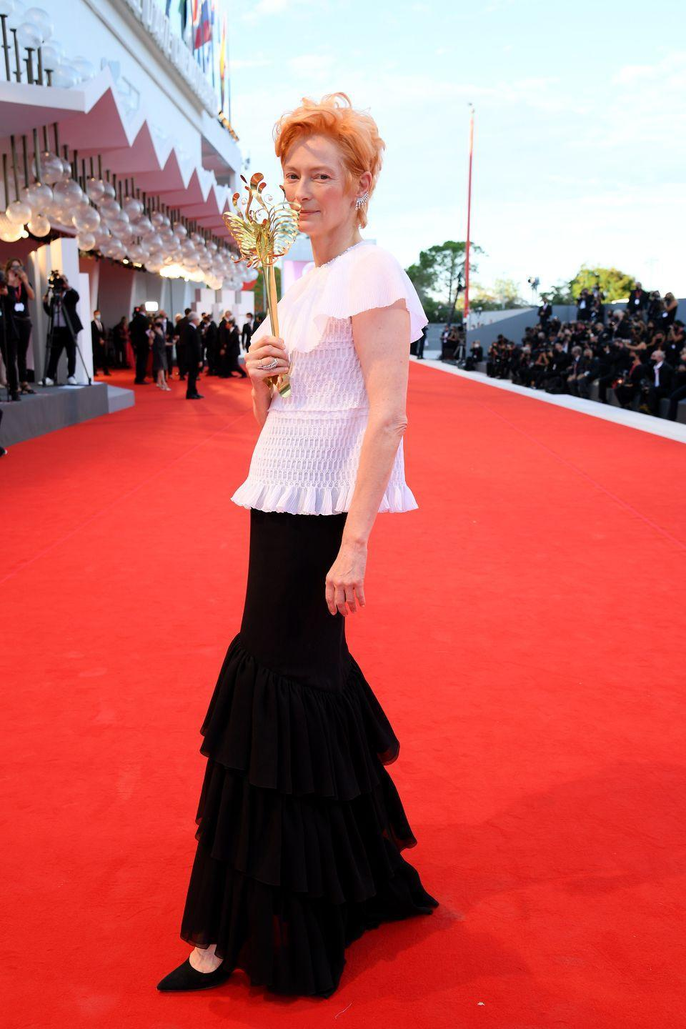 <p>Tilda Swinton wears a white top and black mermaid skirt by Chanel. </p>