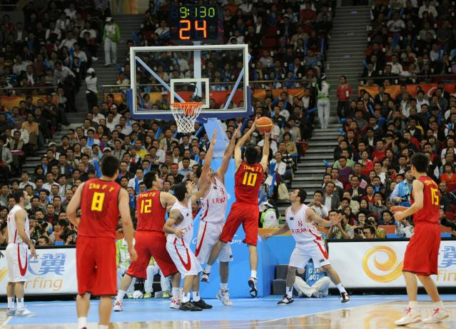 Zhang Zhaoxu of China (10# in red jersey) catches a rebound against Iran during their men's basketball semi-final at the16th Asian Games in Guangzhou on November 25, 2010. China won 68-65. AFP PHOTO/LIU JIN (Photo credit should read LIU JIN/AFP/Getty Images)