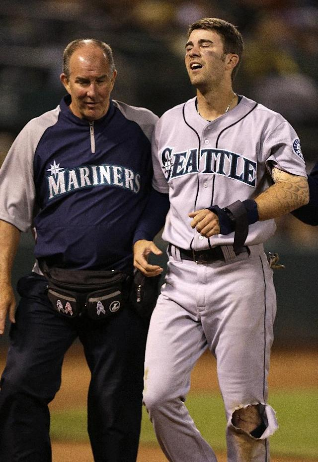 Seattle Mariners' Nick Franklin, right, is assisted off the field by trainer Rick Griffin after injuring his left leg scoring in a play at the plate against Oakland Athletics catcher Derek Norris in the eighth inning of a baseball game Tuesday, Aug. 20, 2013, in Oakland, Calif. (AP Photo/Ben Margot)