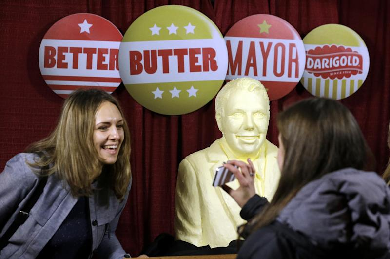 Marianne Goldin smiles as she looks at a photo of her and a butter-sculpture of Seattle mayoral candidate state Sen. Ed Murray before an election night party Tuesday, Nov. 5, 2013, in Seattle. A local dairy company created the promotional sculpture of Murray and also of his challenger, incumbent Mayor Mike McGinn. (AP Photo/Elaine Thompson)