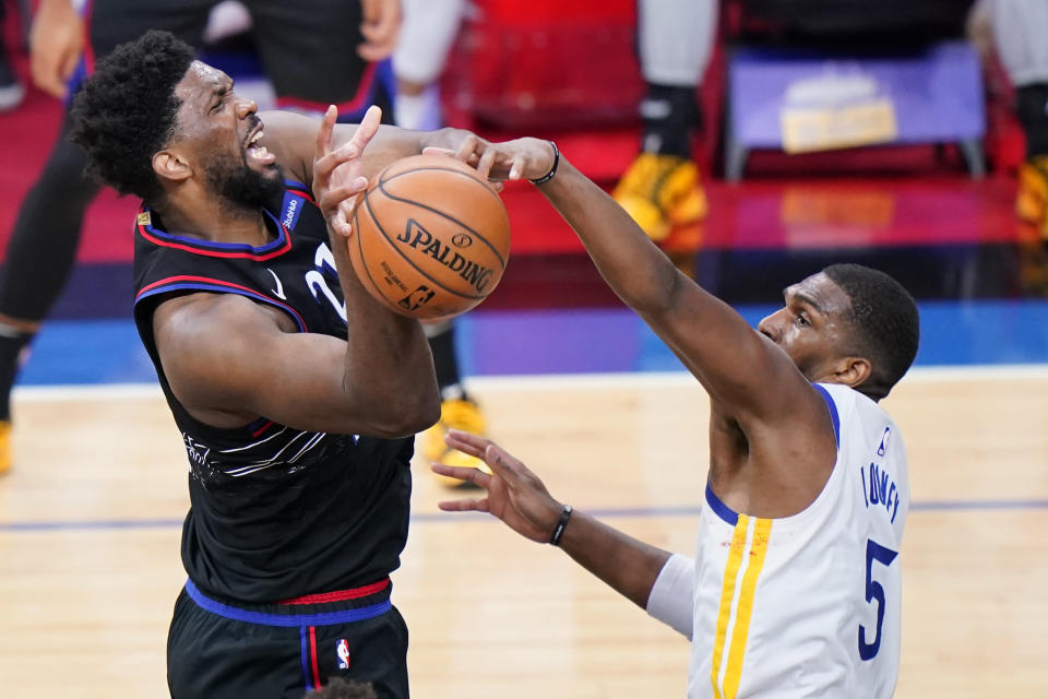 Golden State Warriors' Kevon Looney, right, blocks a shot by Philadelphia 76ers' Joel Embiid during the second half of an NBA basketball game, Monday, April 19, 2021, in Philadelphia. (AP Photo/Matt Slocum)