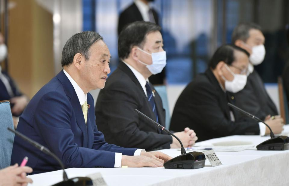 "Japanese Prime Minister Yoshihide Suga, left, attends a cabinet meeting at his official residence in Tokyo Tuesday, April 12, 2021. Japan's government said Tuesday it has decided to start releasing massive amounts of radioactive water stored at the wrecked Fukushima nuclear plant in two years after treatment. Suga told that the government adopted the release to sea as ""most realistic"" and that the disposal of the water is ""unavoidable in order to achieve Fukushima's recovery."" (Yoshitaka Sugawara/Kyodo News via AP)"