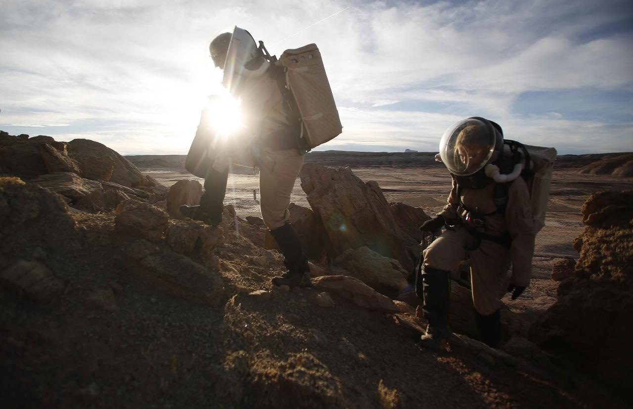 Melissa Battler (L), a geologist and commander of the Crew 125 EuroMoonMars B mission, and Csilla Orgel, a geologist, climb a rock formation to collect geologic samples for study at the Mars Desert Research Station (MDRS) in the Utah desert March 2, 2013. The MDRS aims to investigate the feasibility of a human exploration of Mars and uses the Utah desert's Mars-like terrain to simulate working conditions on the red planet. Scientists, students and enthusiasts work together developing field tactics and studying the terrain. All outdoor exploration is done wearing simulated spacesuits and carrying air supply packs and crews live together in a small communication base with limited amounts of electricity, food, oxygen and water. Everything needed to survive must be produced, fixed and replaced on site. Picture taken March 2, 2013. REUTERS/Jim Urquhart