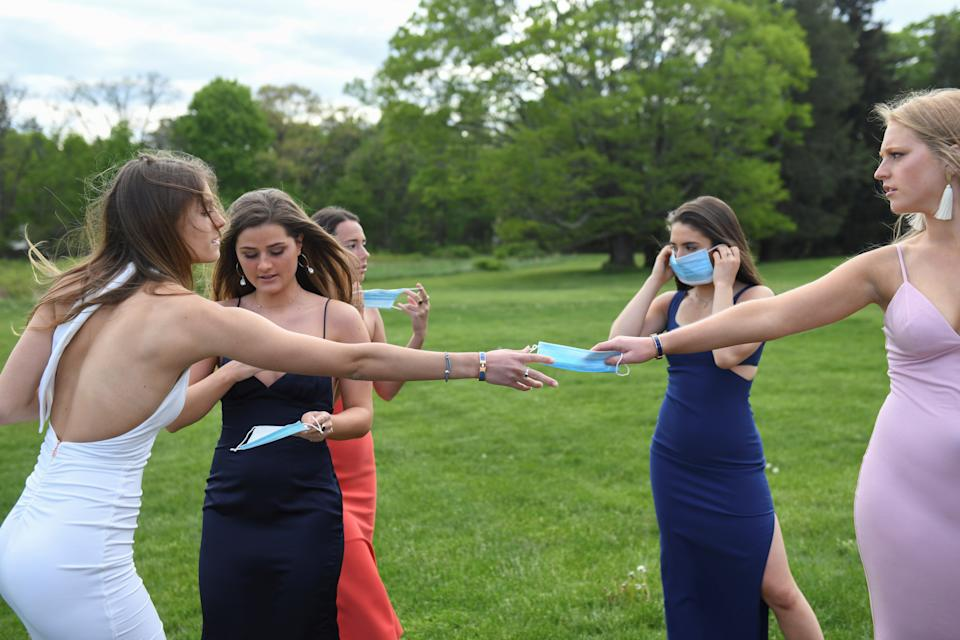 An Iowa school district is planning an in-person prom for sprirng, but is still unsure what that will look like. Here, students in Massachusetts pose for photos in prorm dresses after their prom was canceled in May of last year. (Photo: REUTERS/Faith Ninivaggi)