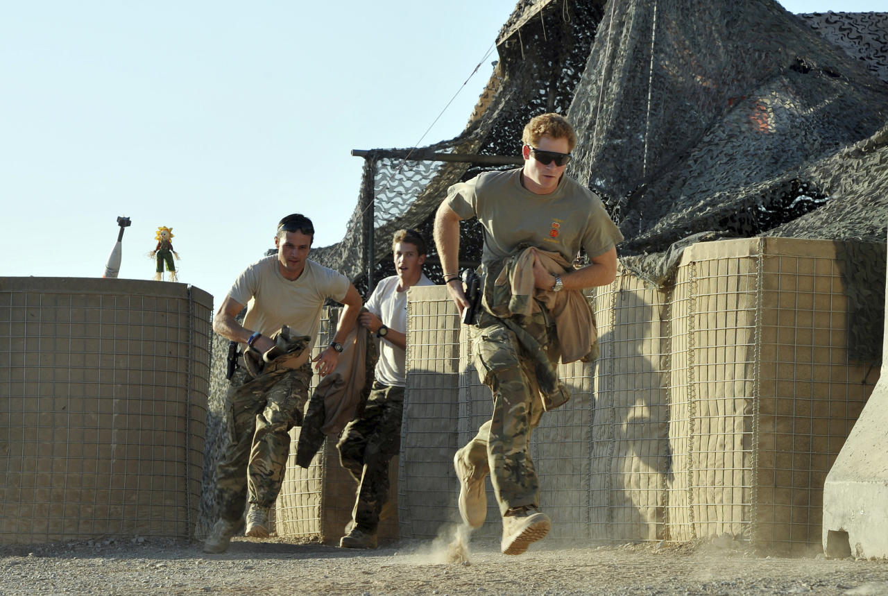 Prince Harry races out from the VHR (very high ready-ness) tent with fellow crew members, to scramble his Apache helicopter at Camp Bastion, southern Afghanistan in this photograph taken November 3, 2012. REUTERS/John Stillwell/Pool