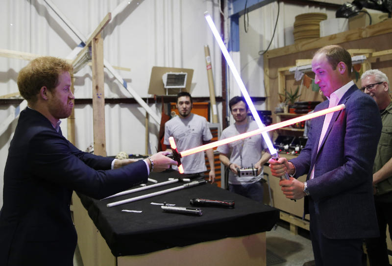 Prince Harry (L) and Prince William, Duke of Cambridge try out lightsabers during a tour of the Star Wars sets at Pinewood studios on April 19, 2016 in Iver Heath, England. Prince William and Prince Harry are touring Pinewood studios to visit the production workshops and meet the creative teams working behind the scenes on the Star Wars films.